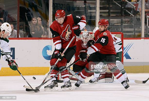 Michael Stone and Boyd Gordon of the Arizona Coyotes battle for the puck with Chris Porter of the Minnesota Wild during the second period at Gila...