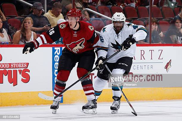 Michael Stone of the Arizona Coyotes and Joel Ward of the San Jose Sharks in action during the NHL preseason game at Gila River Arena on October 2...