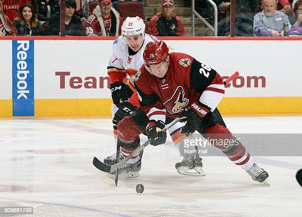 Michael Stone of the Arizona Coyotes and Mikael Backlund of the Calgary Flames battle for the puck during the first period at Gila River Arena on...