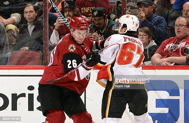 Michael Stone of the Arizona Coyotes battles with Michael Frolik of the Calgary Flames along the boards during the second period at Gila River Arena...