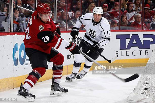 Michael Stone of the Arizona Coyotes centers the puck ahead of Milan Lucic of the Los Angeles Kings during the second period of the NHL game at Gila...