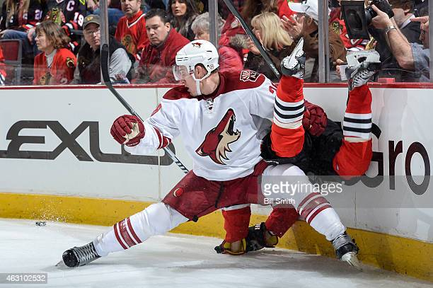 Michael Stone of the Arizona Coyotes collides with a Chicago Blackhawks player during the NHL game at the United Center on February 9 2015 in Chicago...