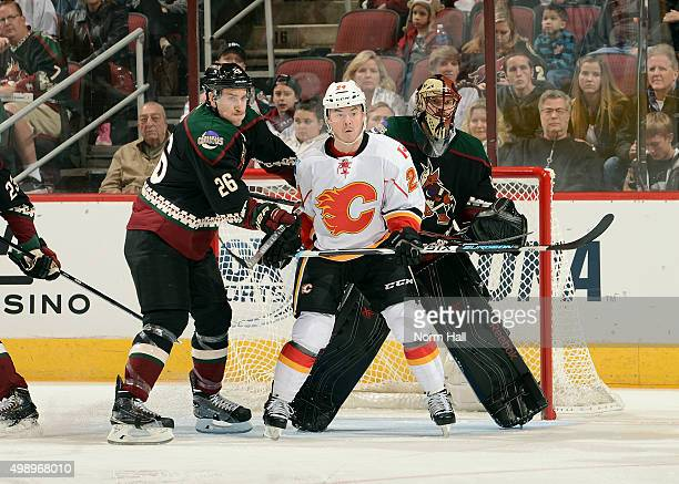Michael Stone of the Arizona Coyotes gives a shove to Jiri Hudler of the Calgary Flames as he positions himself in front of goaltender Mike Smith of...