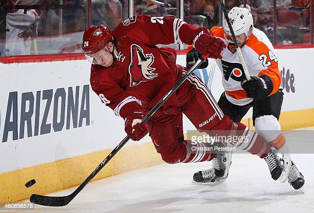 Michael Stone of the Arizona Coyotes is checked off the puck from Matt Read of the Philadelphia Flyers during the second period of the NHL game at...