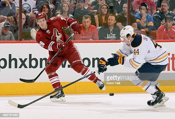Michael Stone of the Arizona Coyotes passes the puck under the stick of Nicolas Deslauriers of the Buffalo Sabres during the first period at Gila...