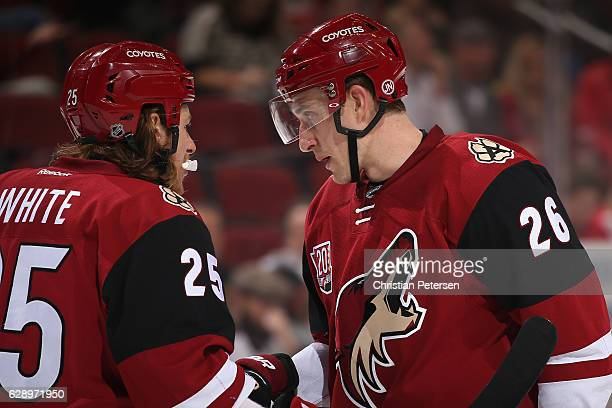Michael Stone of the Arizona Coyotes talks with Ryan White during the second period of the NHL game against the Calgary Flames at Gila River Arena on...