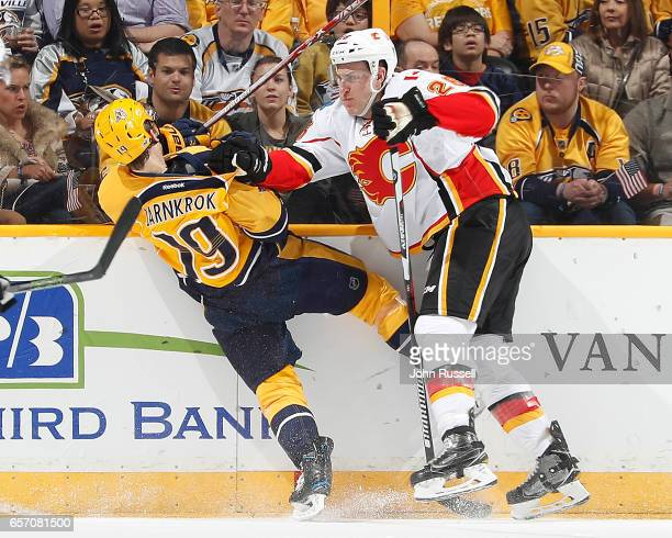 Michael Stone of the Calgary Flames checks Calle Jarnkrok of the Nashville Predators during an NHL game at Bridgestone Arena on March 23 2017 in...