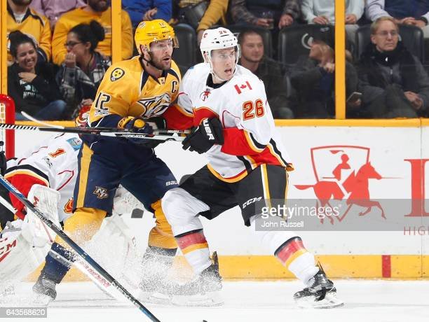 Michael Stone of the Calgary Flames defends against Mike Fisher of the Nashville Predators during an NHL game at Bridgestone Arena on February 21...