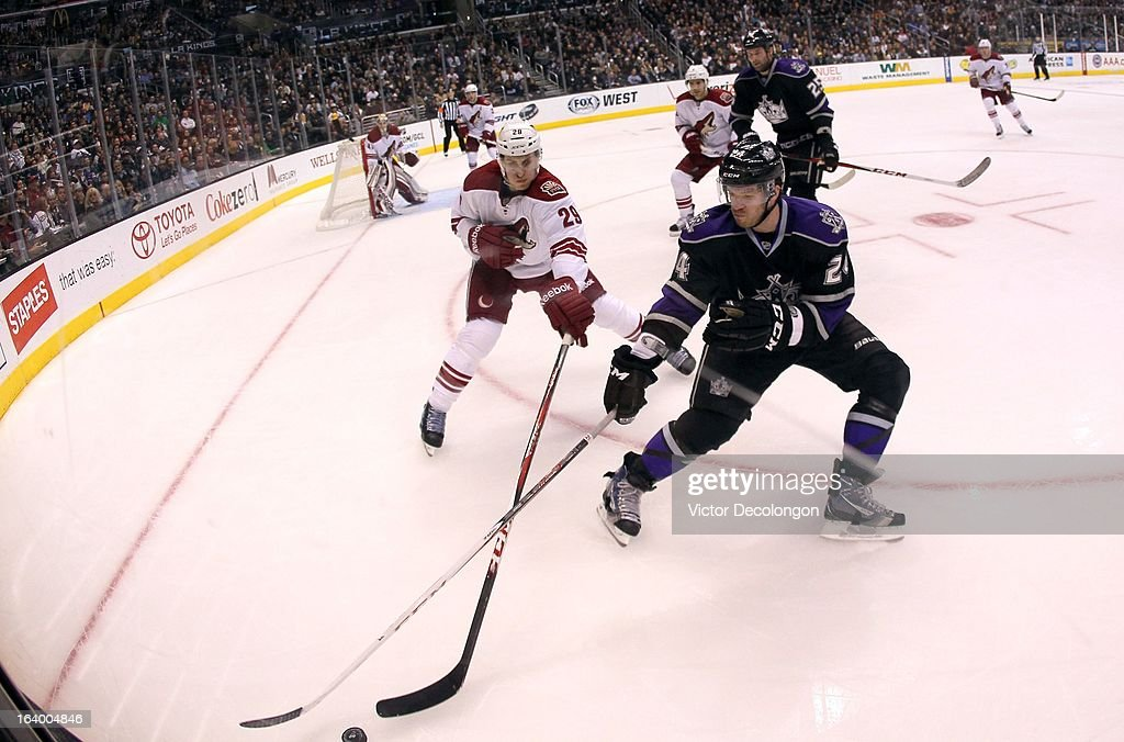 Michael Stone #29 of the Phoenix Coyotes and Colin Fraser #24 of the Los Angeles Kings vie for the puck in the corner during the NHL game at Staples Center on March 18, 2013 in Los Angeles, California. The Kings defeated the Coyotes 4-0.
