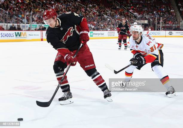 Michael Stone of the Phoenix Coyotes handles the puck ahead of TJ Galiardi of the Calgary Flames during the second period of the NHL game at...