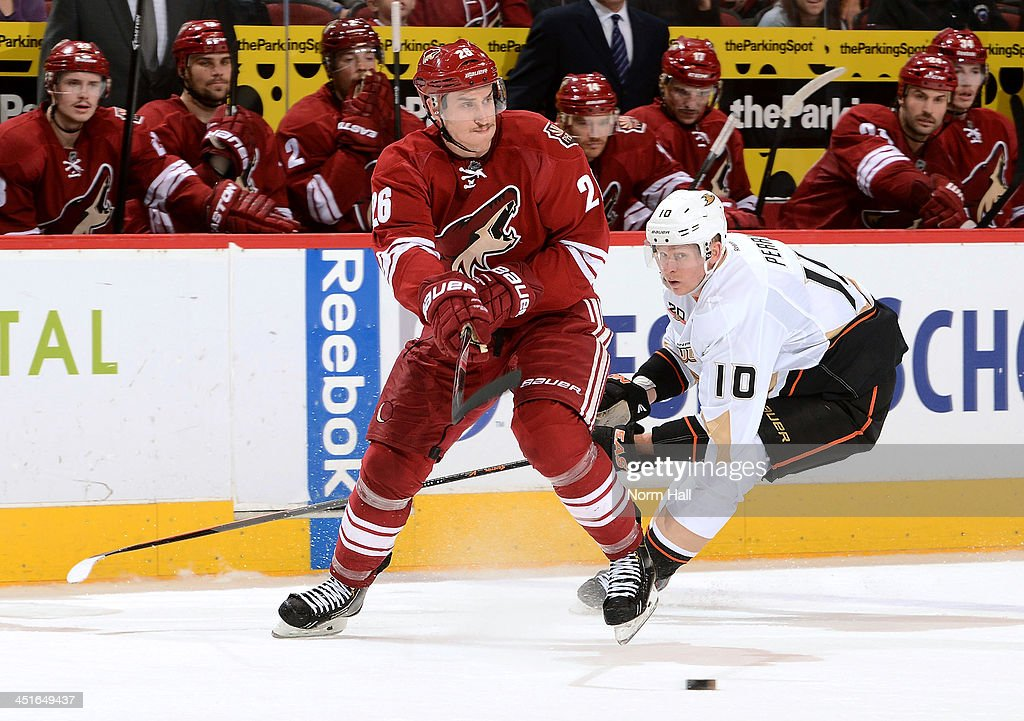 Michael Stone #26 of the Phoenix Coyotes passes the puck as <a gi-track='captionPersonalityLinkClicked' href=/galleries/search?phrase=Corey+Perry&family=editorial&specificpeople=213864 ng-click='$event.stopPropagation()'>Corey Perry</a> #10 of the Anaheim Ducks defends during the third period at Jobing.com Arena on November 23, 2013 in Glendale, Arizona.