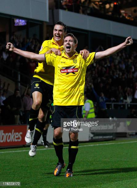 Michael Symes of Burton Albion celebrates with teammate Jack Dyer after scoring their second goal during the Capital One Cup Second Round match...