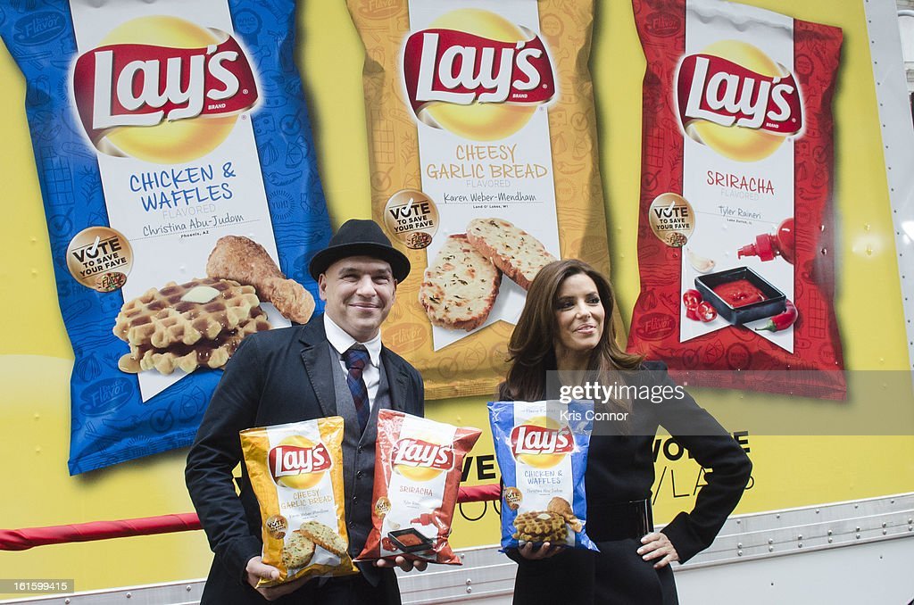Michael Symon and <a gi-track='captionPersonalityLinkClicked' href=/galleries/search?phrase=Eva+Longoria&family=editorial&specificpeople=202082 ng-click='$event.stopPropagation()'>Eva Longoria</a> pose for a photo for photographers during NYSE Celebrates Lay's 'Do Us a Flavor' Contest Finalists during the opening bell at New York Stock Exchange on February 12, 2013 in New York City.
