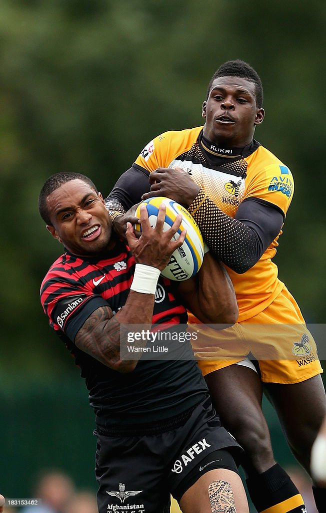 Michael Tagicakibau of Saracens tussles with Christian Wade of London Wasps during the Aviva Premiership match between Saracens and London Wasps at Allianz Park on October 5, 2013 in Barnet, England.