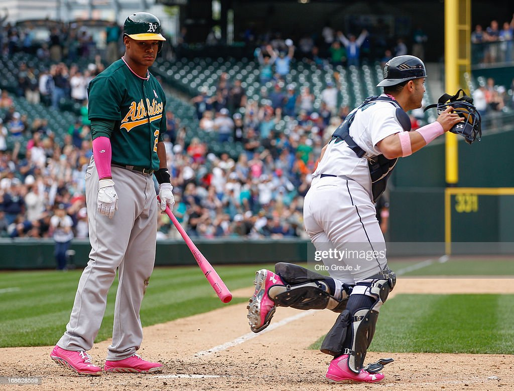 Michael Taylor #23 of the Oakland Athletics looks on after striking out for the final out as catcher <a gi-track='captionPersonalityLinkClicked' href=/galleries/search?phrase=Jesus+Montero&family=editorial&specificpeople=4900196 ng-click='$event.stopPropagation()'>Jesus Montero</a> #63 of the Seattle Mariners heads to the mound to celebrate at Safeco Field on May 12, 2013 in Seattle, Washington.