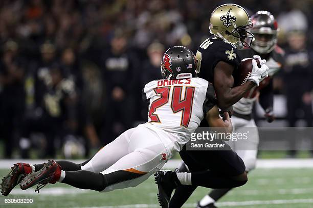 Michael Thomas of the New Orleans Saints is tackled by Brent Grimes of the Tampa Bay Buccaneers at the MercedesBenz Superdome on December 24 2016 in...