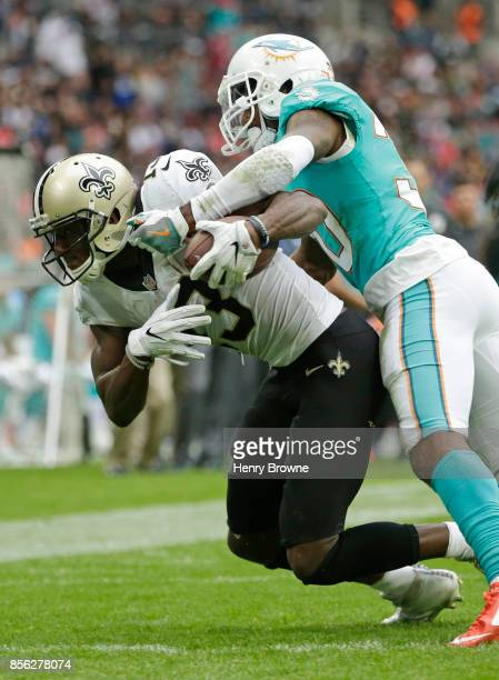 Michael Thomas of the New Orleans Saints scores a touchdown despite the efforts of Cordrea Tankersley of the Miami Dolphins during the NFL game...