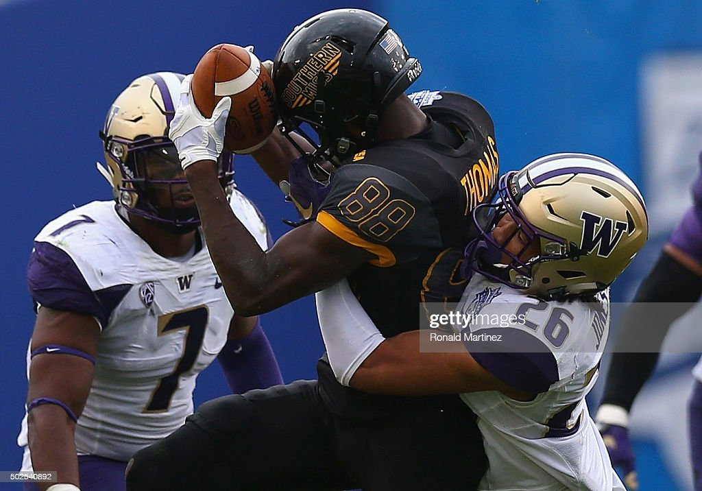 Michael Thomas of the Southern Miss Golden Eagles makes a pass reception against Sidney Jones of the Washington Huskies during the Zaxby's Heart of...