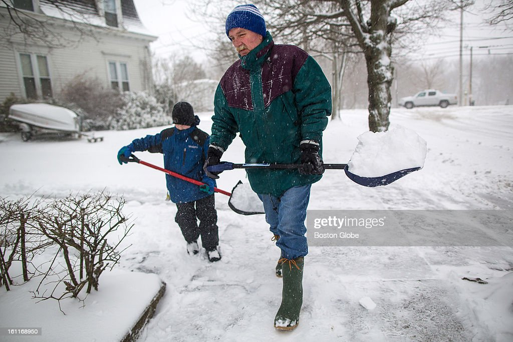 Michael Tilley, 8, left, helped his grandfather Scott Tilley shovel the sidewalk as a winter storm, expected to dump as much as 24 inches of snow in the region, intensified in Newburyport.