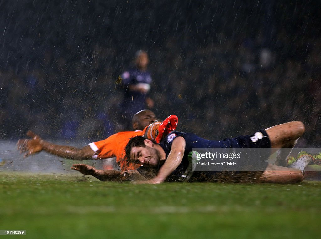 Michael Timlin of Southend slides through the mud after being tackled by Millwall defender Danny Shittu during the FA Cup Third Round match between Southend and Millwall at Roots Hall on January 4, 2014 in Southend, England.