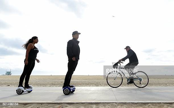Michael Tran and Katie Rodriguez pass a cyclist on their Hoverboards while displaying ease of use on the Venice Beach Boardwalk on December 10 2015...