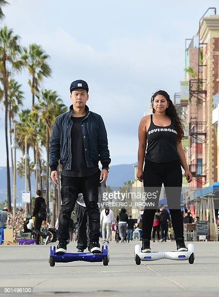 Michael Tran and Katie Rodriguez use their Hoverboards while displaying ease of use on the Venice Beach Boardwalk on December 10 2015 The hot item on...