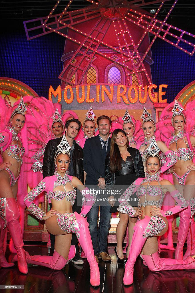 Michael Trevino, Matthew Davis and Jenna Ushkowitz pose backstage with the dancers of the Moulin Rouge after they have attended the show at Le Moulin Rouge on May 22, 2013 in Paris, France.