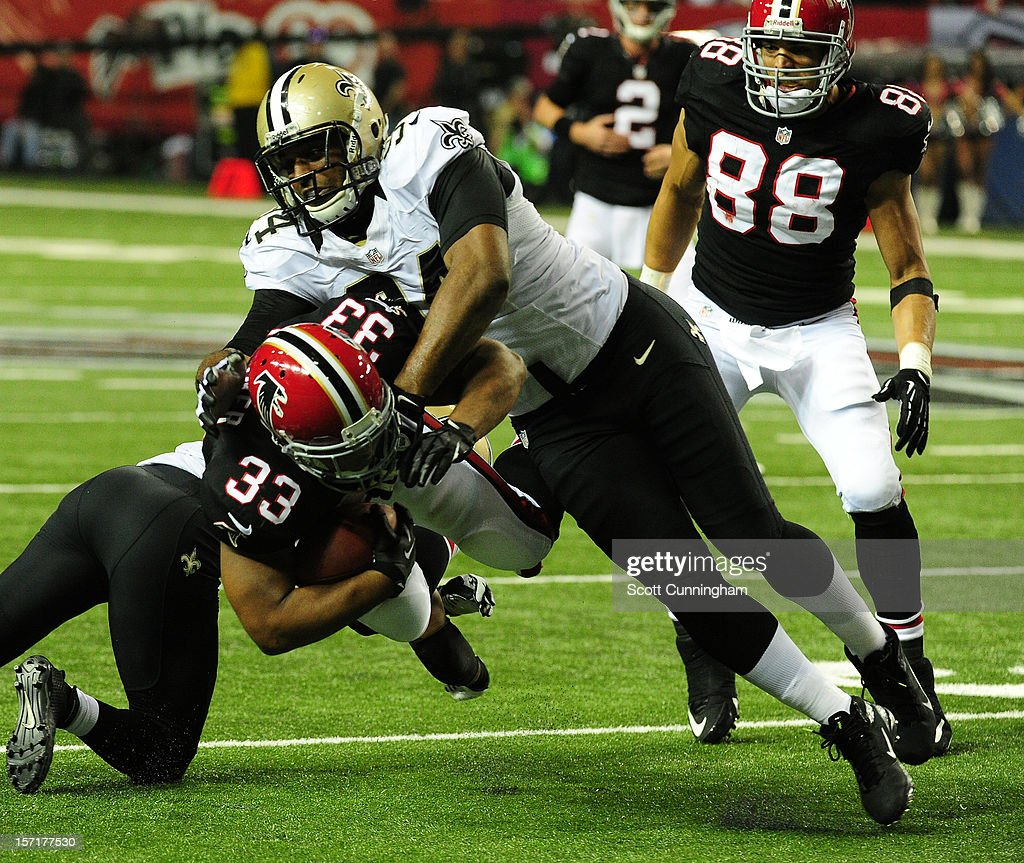 Michael Turner #33 of the Atlanta Falcons is tackled by Cameron Jordan #94 of the New Orleans Saints at the Georgia Dome on November 29, 2012 in Atlanta, Georgia