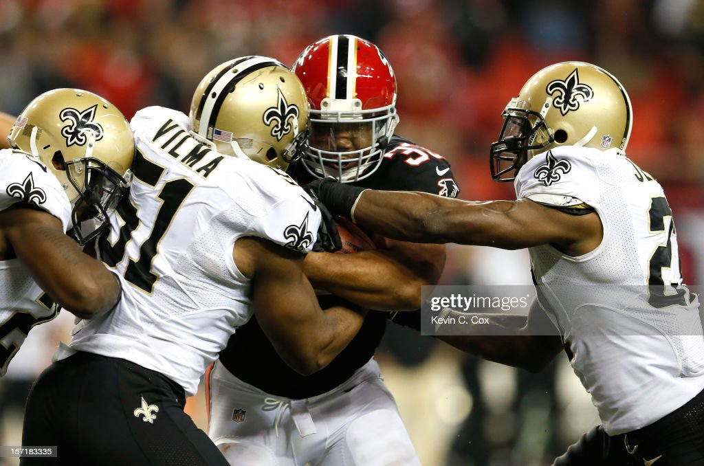Michael Turner #33 of the Atlanta Falcons is tackled by Rafael Bush #25 and Jonathan Vilma #51 and Malcolm Jenkins #27 of the New Orleans Saints prior to fumbling the ball at Georgia Dome on November 29, 2012 in Atlanta, Georgia.