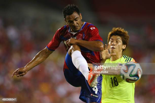 Michael Umana of Costa Rica clears the ball under pressure from Yuya Osako of Japan during the International Friendly Match between Japan and Costa...