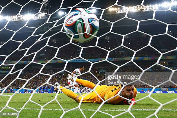 Michael Umana of Costa Rica shoots and scores his penalty kick past Orestis Karnezis of Greece to defeat Greece in a shootout during the 2014 FIFA...