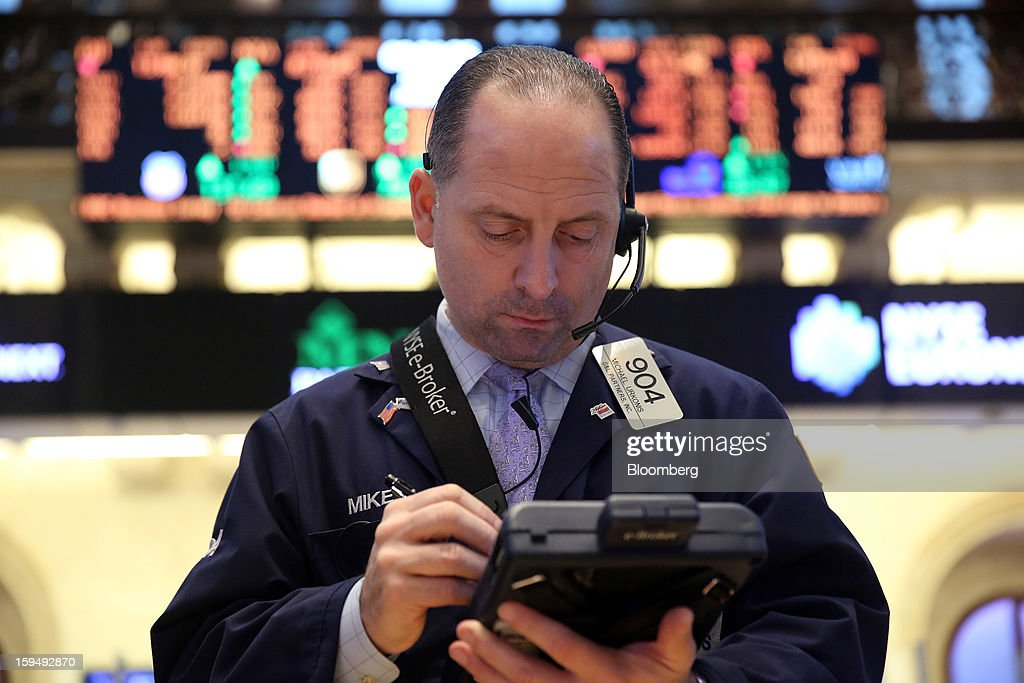 Michael Urkonis, a trader with G&L Partners Inc., works at the New York Stock Exchange (NYSE) in New York, U.S., on Monday, Jan. 14, 2013. U.S. stocks fell, after the Standard & Poor's 500 Index climbed for two weeks to trade near the highest level in five years, as Apple Inc. tumbled amid a report it cut orders for iPhone components. Photographer: Scott Eells/Bloomberg via Getty Images
