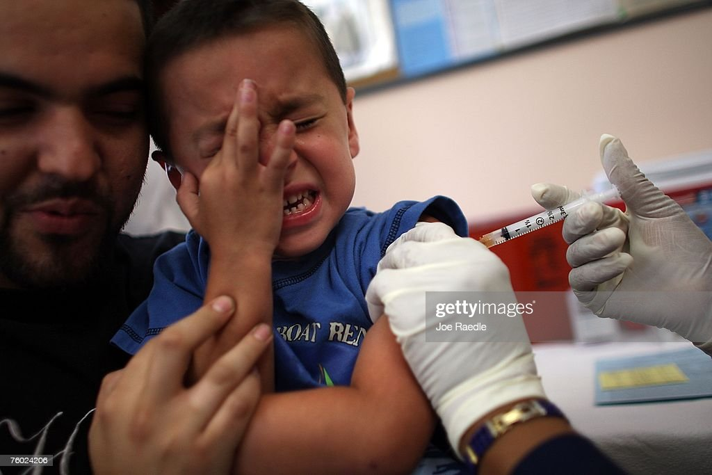 Michael Valdivia holds, Jakob Gutierrez, 5, as he receives an immunization shot from school nurse Barbara Dale on August 8, 2007 in Hialeah, Florida. The free immunization is part of the Miami-Dade County Health Department's program to help children heading back to school.