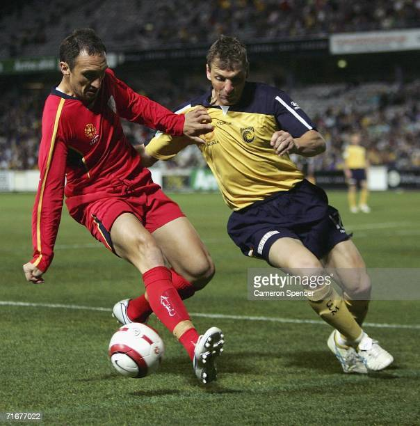 Michael Valkanis of Adelaide United contests the ball with Stewart Petrie of the Mariners during the ALeague PreSeason Cup Final between the Central...