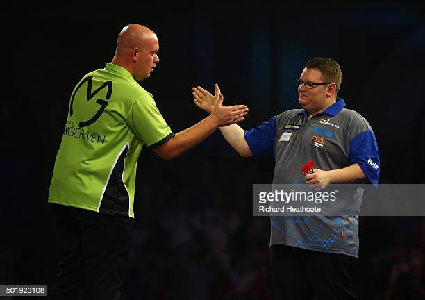 Michael van Gerwen consoles Rene Eidams after narrowly beating Eidams in their first round match on day two of the 2016 William Hill PDC World Darts...