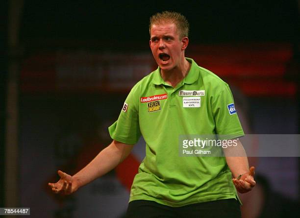 Michael van Gerwen of Netherlands celebrates winning a leg during the first round match between Phil Taylor of England and Michael van Gerwen of...