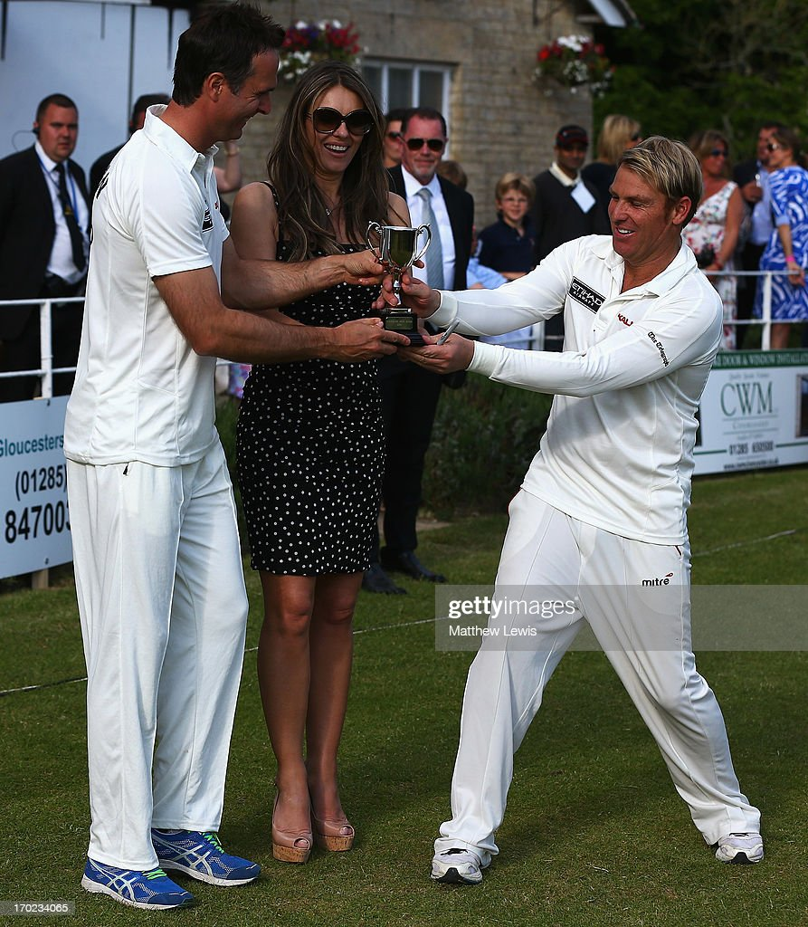 Michael Vaughan, captain of Michael Vaughan's England and Shane Warne, captain of Shane Waren's Australia are presented with the trophy by Elizabeth Hurley after the match was a draw after the Shane Warne's Australia vs Michael Vaughan's England T20 match at Circenster Cricket Club on June 9, 2013 in Cirencester, England.
