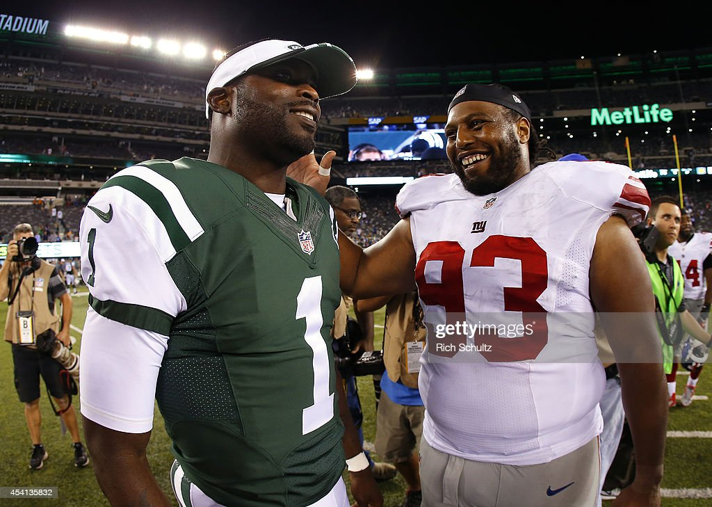 Michael Vick of the New York Jets talks with Mike Patterson of the New York Giants after their NFL preseason game at MetLife Stadium on August 22...