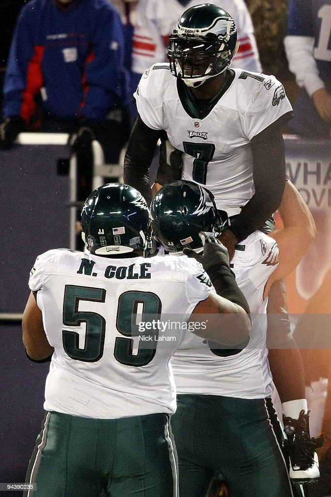 Michael Vick #7 of the Philadelphia Eagles celebrates after scoring a touchdown in the second quater with Todd Herremans #79 and Nick Cole #59 against the New York Giants at Giants Stadium on December 13, 2009 in East Rutherford, New Jersey.