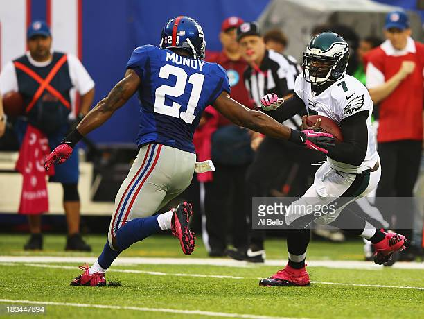Michael Vick of the Philadelphia Eagles scrambles against Ryan Mundy of the New York Giants during their game at MetLife Stadium on October 6 2013 in...