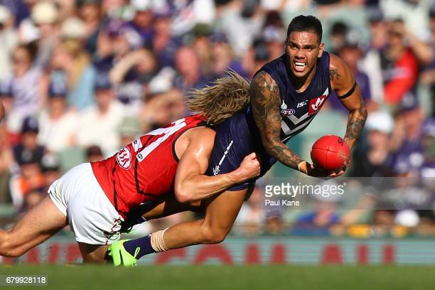 Michael Walters of the Dockers looks to handball while being tackled by Dyson Heppell of the Bombers during the round seven AFL match between the...