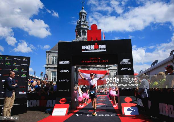 Michael Weiss from Austria crosses the Ironman arch at the finish line with the flag of his country during the Ironman MaastrichtLimburg on August 6...