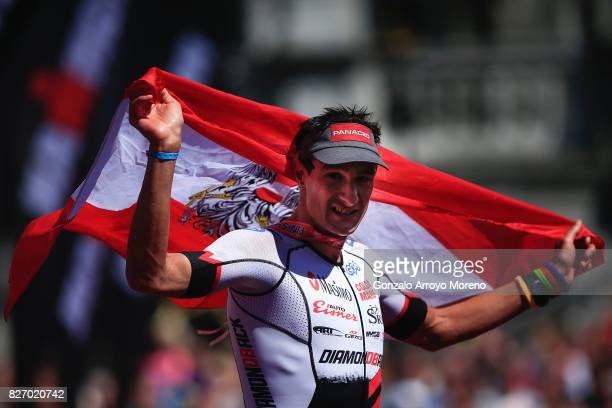 Michael Weiss from Austria runs with the flag of his country at the finish line of the Ironman MaastrichtLimburg on August 6 2017 in Maastricht...