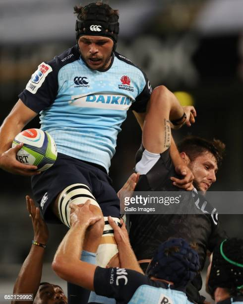 Michael Wells of the NSW Waratahs jumps over Ruan Botha of the Cell C Sharks during the Super Rugby match between the Cell C Sharks and Waratahs at...
