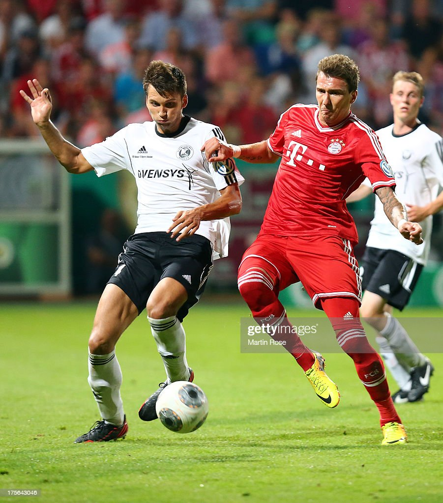 Michael Wessel (L) of Rehden and Mario Mandzukic (R) of Muenchen battle for the ball during the DFB Cup first round match between BSV SW Rehden and Bayern Muenchen at osnatel Arena on August 5, 2013 in Osnabrueck, Germany.