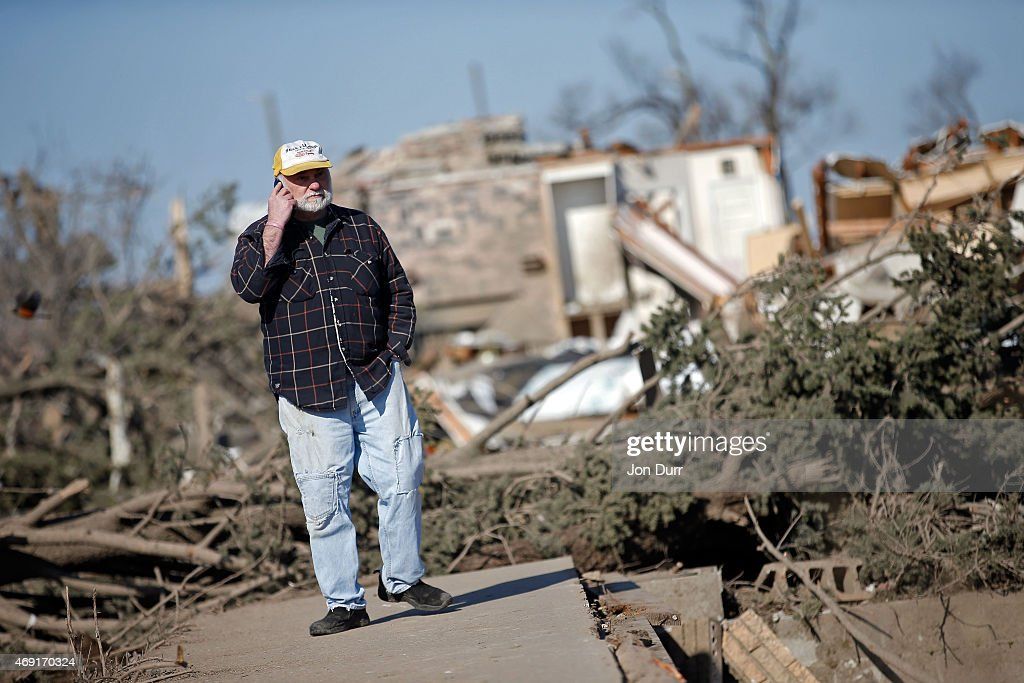 Michael West surveys the damage of his mother's home on IL64 after a tornado swept through the night before on April 10 2015 in Rochelle Illinois...