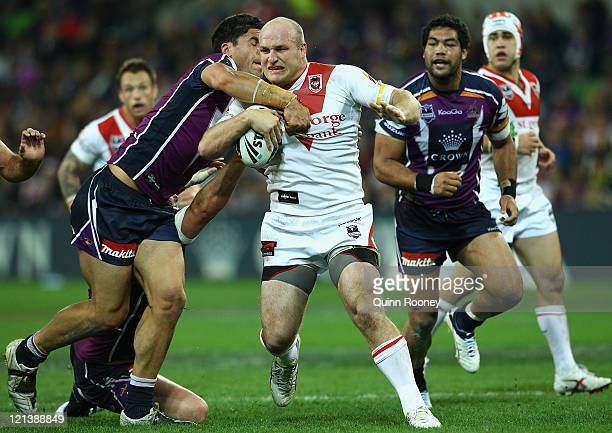 Michael Weyman of the Dragons is tackled by Jesse Bromwich of the Storm during the round 24 NRL match between the Melbourne Storm and the St George...