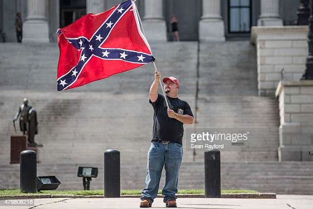 Michael Whitaker shows his support for the Confederate flag as lawmakers vote on removing the Confederate Flag from the capitol grounds at the South...