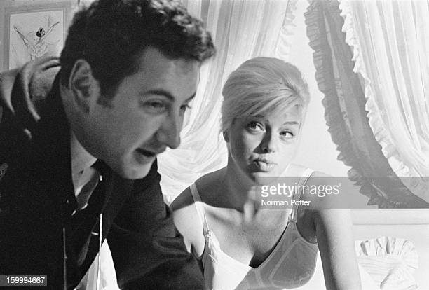 Michael Winner directs English actress Diana Dors in a bedroom scene for the crime drama 'West 11' London 28th January 1963
