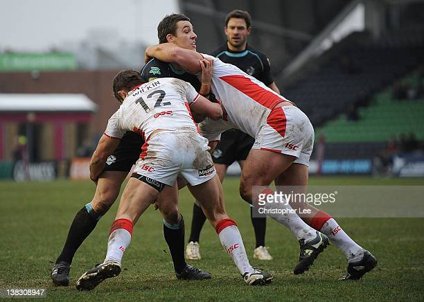 Michael Witt of London Broncos is tackled by Jon Wilkin and Josh Perry of St Helens during the Stobart Super League match between London Broncos and...
